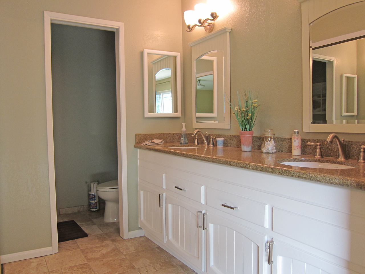 Remodeled master bathroom with tile floors and granite counter top.