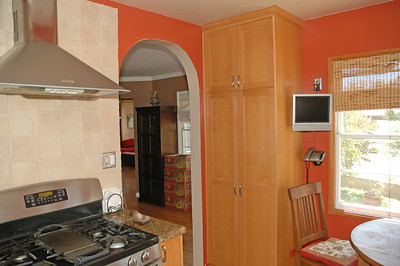 The kitchen features stainless stell appliances...note the large hood over the gas stove.
