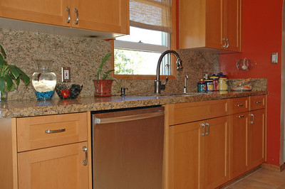 The granite countertops have a high backsplash.