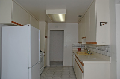 Galley style kitchen includes refridgerator.