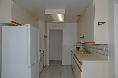 Galley style kitchen includes refridgerator.