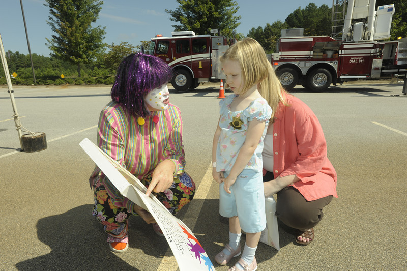 Firefighter/EMT (clown) Lt Wanda Maddicks explains a drug safety handbook with Amelia Lenz and Nicole Renolds