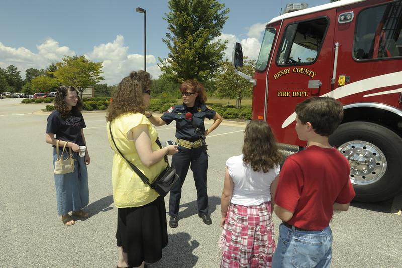 Firefighter/EMT Slagle shows a Henry Co. family how the HCFD ladder truck works