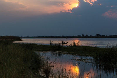 Lower Zambezi River, Zambia Fishermen gather their nets at the end of the day on the Zambezi River.