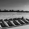 Boats resting on icy Charles River, on Cambridge side, with the Boston sky line in the background.