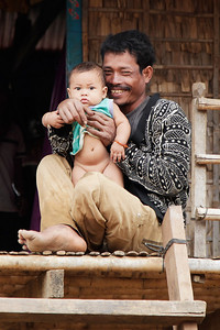 near Tonlé Sap Lake, Cambodia A father holds up his baby as we walk by in the fishing village near Tonlé Sap Lake.