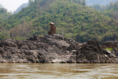 northern Laos A broken navigation aid above rocks in the Mekong River.