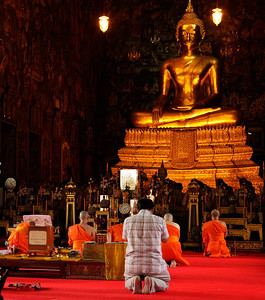 Bangkok, Thailand Praying at Wat Suthat Thep Wararam. At 25 feet tall, Phra Si Sakyamuni Buddha is famous for being one of the largest cast bronze images of Buddha in the entire country.