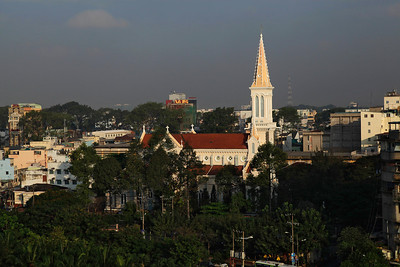 Saigon  (Ho Chi Minh City), Vietnam A church tower rises in the early sunlight in District 1 of Saigon.