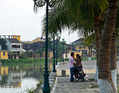 Hội An, Vietnam A couple sits on a motorcycle along the riverfront area of Hội An.