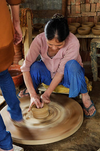 Hội An, Vietnam A Vietnamese woman working at a pottery wheel in Hội An. The wheel which is human powered, is being turned by a family member. This family has been producing local pottery for over 800 years. Unfortunately, the younger members of the family can get better paying jobs in the city. If none of them change their mind about taking over the family business, the craft will die with this generation.