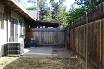 Private fenced yard with a concrete  patio slab...faces West