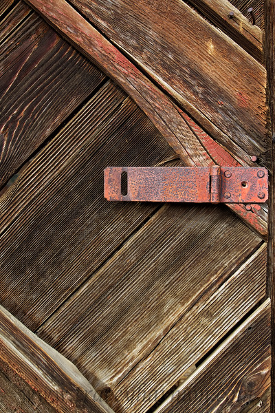 A weathered wooden gate with it's hasp closure left undone.