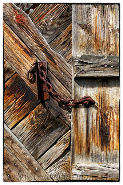 A sun-baked wooden gate and it's positive closure, a stout piece of chain.