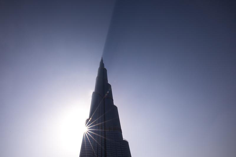 Burj Khalifa casting a shadow through clouds during a sunrise.