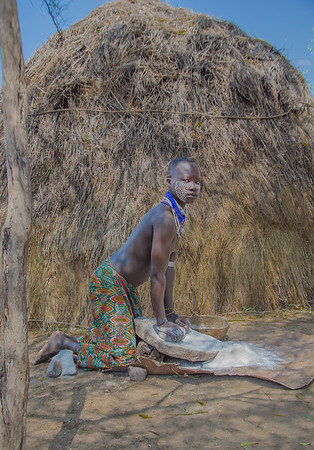 Mursi man grinding millet using a traditional grinding stone