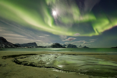 Norway, Lofoten: Northern lights shimmer over an icy stream as it winds its way across the sand at Haukland Beach in northern Norway.