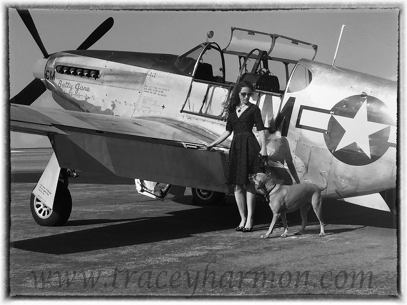 "Kassidy Harmon and her dog Lucy pose in front of ""Betty Jane"", a Mustang Bomber."