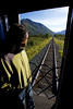Alejandro watches the rails fall away as the train crawls up the grade that eventually leads to the pass above Seward.