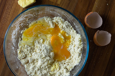 Cracked eggs in a clear bowl of flour and cheese
