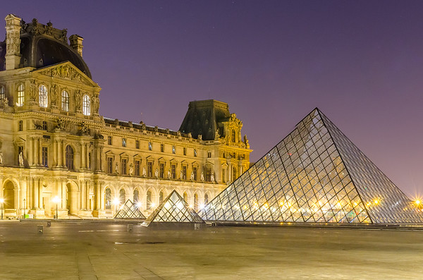 The main courtyard (Cour Napoléon) of the Louvre Palace at night