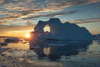Sunburst behind an iceberg with a hole in it.