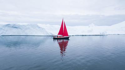 Beautiful red sailboat next to a massive iceberg.