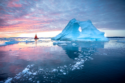 Red sailboat cruising among icebergs.