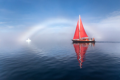 Beautiful red sailboat under a glowing fog bow.