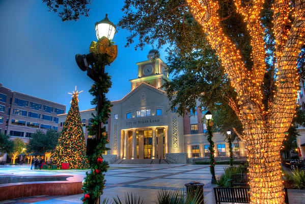 Sugar Land Christmas<br /> I've taken photos here before. It's close to work and it has a small town charm, which is hard to find in a suburb of Houston. Like many places around the country, the Sugar Land Town Center places a large Christmas tree and lots of lights on adjoining buildings, making for a festive atmosphere. The challenge is finding it when it's not full of people. What better opportunity than on a slow Tuesday evening and add in a lite mist and the area was almost empty. The local mall, however, was a different story.