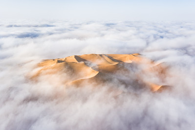 Aerial view of a sand dune surrounded by fog.