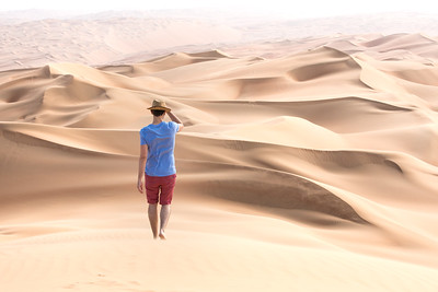 Young tourist in shorts hiking in giant dunes.
