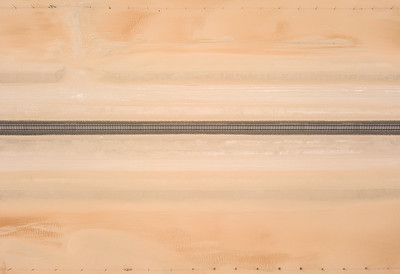 Straight railroad track passing through a sandy desert.