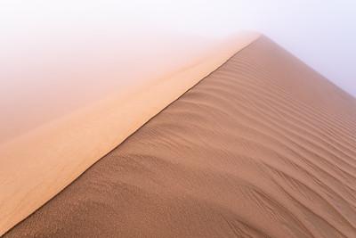 Sand dune in dense fog.