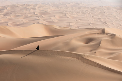 Young woman in Abaya posing in desert landscape.