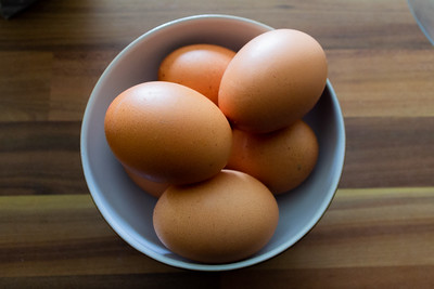 Six eggs stacked in a white bowl