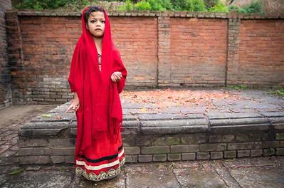 Beautiful young girl in a red dress ahead of a ceremony.