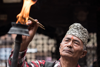 An elderly man participating in a ceremonial procession.