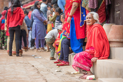 Elderly ladies watching a passing ceremony procession.