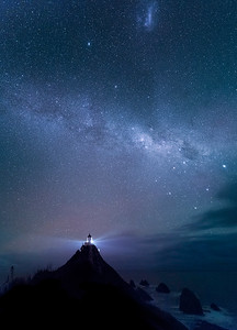 Nugget Point, South Island, New Zealand: The Milky Way over Nugget Point lighthouse. A Magellanic Cloud, visible only in the Southern Hemisphere, is at the top of the picture.