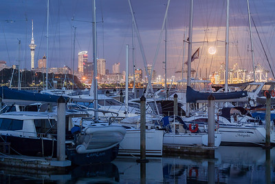 Auckland, North Island, New Zealand: Moonset over the Auckland skyline looking through the boats at the docks of the Royal Akarana Yacht Club.