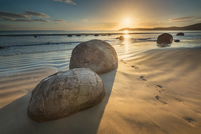 Koekohe Beach, South Island, New Zealand: Footsteps in the sand next to some of the Moeraki Boulders as the sun rises on the horizon.