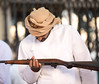 Omani man investigating a gun on a gun market.