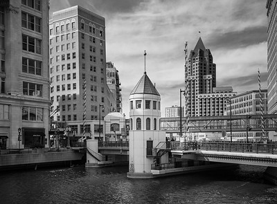 """The River Bridge Tower along the Milwaukee Riverwalk in downtown. The Riverwalk is a 20-block pedestrian promenade along the Milwaukee River. There are two skybridges visible in this photo, part of the Milwaukee Skywalk System, affectionately referred to as """"Skywaukee"""". Downtown is peppered with nine such skybridges spanning a skywalk of 1.75 miles (2.8 km), which encourages pedestrian traffic throughout the downtown area during the winter's heavy weather."""
