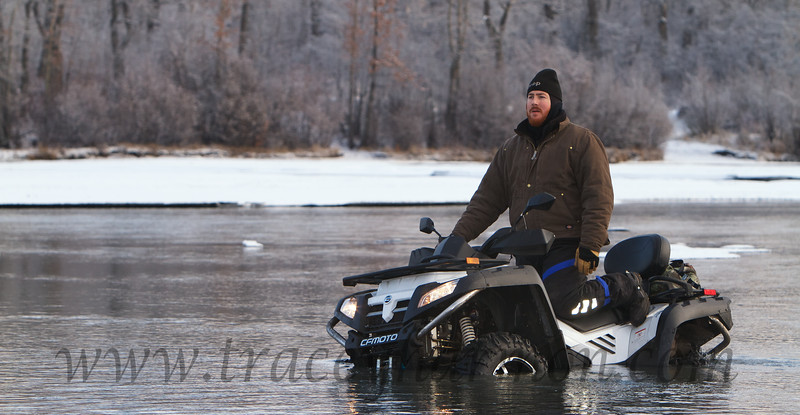 "Paul Persian sits it out on his atv, waiting for a tow line after ""locating"" a silt-filled hole in Jim's Creek, Alaska."