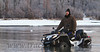 """Paul Persian sits it out on his atv, waiting for a tow line after """"locating"""" a silt-filled hole in Jim's Creek, Alaska."""