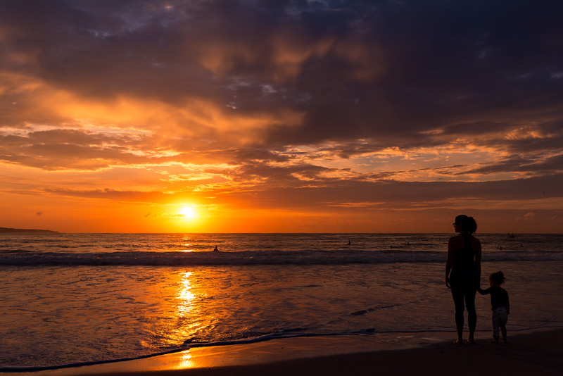 A mother and her daughter watching the sunrise