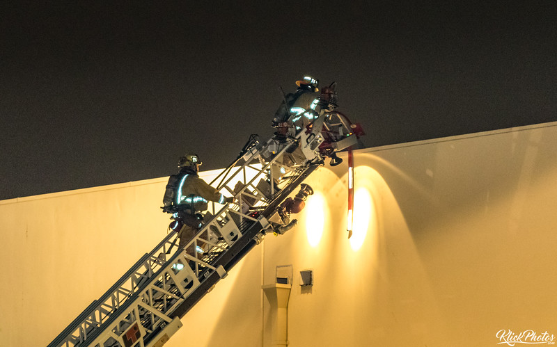 Firefighters use a ladder truck to access to the roof of the Seafood City Supermarket in Irvine after a fire broke out early Friday morning.