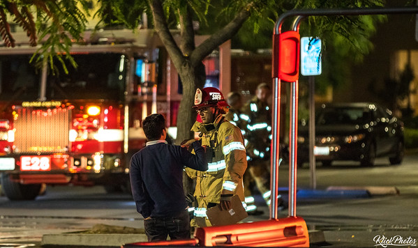A responsible party speaks with a fireman on scene of a 2nd alarm fire that broke out at the Seafood City Supermarket in Irvine early Friday morning.