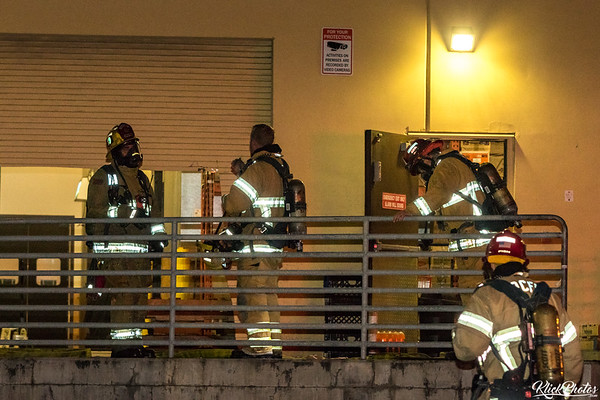 Firefighters discuss tactics at the rear entrance to the Seafood City Supermarket in Irvine after a fire broke out early Friday morning.